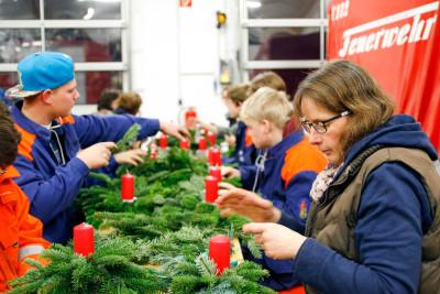 Fleißig ging es beim Basteln der Adventsgestecke im Holtorfer Feuerwehrhaus zu. Foto: Henkel