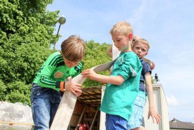 """""""Feuerwehr und Teamarbeit sind zwei unzertrennliche Dinge"""" und dies mussten die Kinder an mehreren Stationen beweisen. Beispielsweise um einen Tischtennisball durch einen Feuerwehrschlauch zu transportieren. Foto: Titze"""