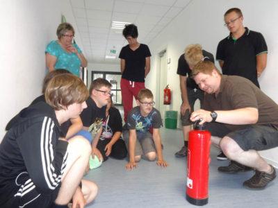 Lehrer Martin Siegfried erklärt einen Feuerlöscher. Foto: Koch
