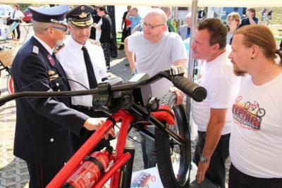Beim Rundgang wurde auch der Präsident des Deutschen Feuerwehrverbands Hartmut Ziebs (2. v.l.) auf das Bike aufmerksam. Foto: Ortec