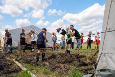 Während die einen den Graben erweitern sorgten im Hintergrund Jugendliche für Nachschub an Rindenmulch. Foto: Henkel