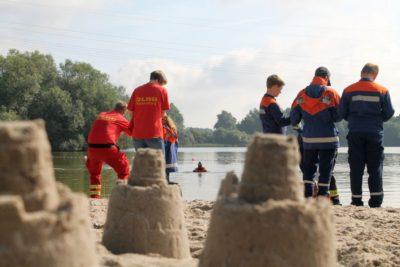 Hinter den letzten Sandburgen am Sander See fand die Einweisung statt, um Recca Weber von der DLRG aus dem Wasser zu ziehen. Foto: Wolfgang Kaul